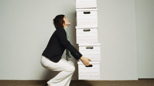Woman Carefully Carrying Boxes
