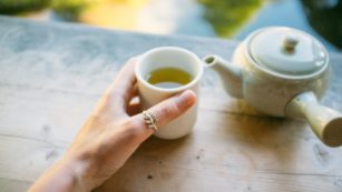 Cropped Hand Holding Green Tea Cup By Teapot On Table